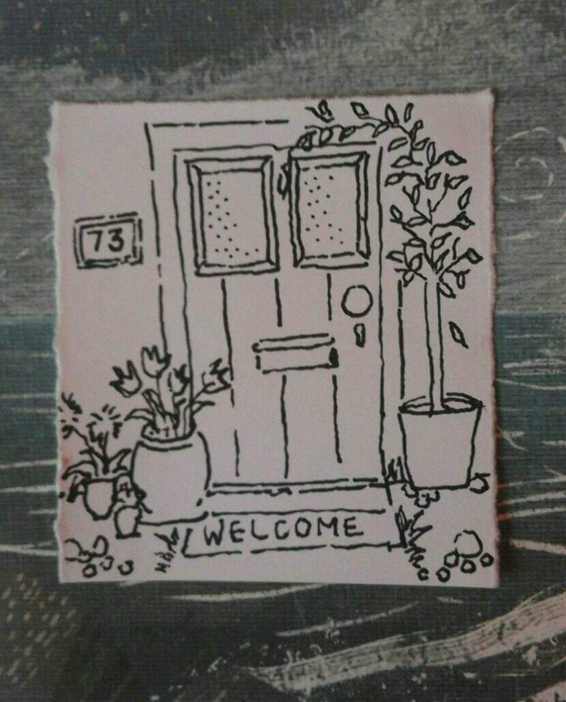"""a photograph of a small ink drawing on paper, against a painted canvas background that is dark grey with white textured paint marks. The drawing is of a door with plants on both sides, with a mat that says """"welcome"""" at the foot. There is a sign with a number """"73"""" on the left side of the door."""